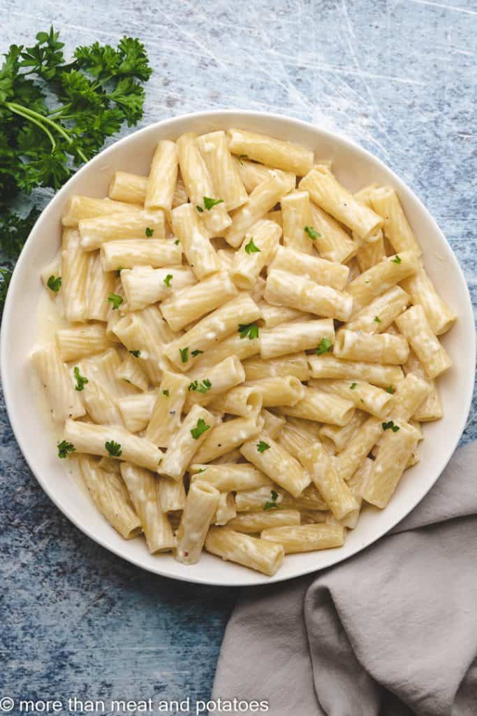 A top-down view of the garlic pasta topped with parsley.