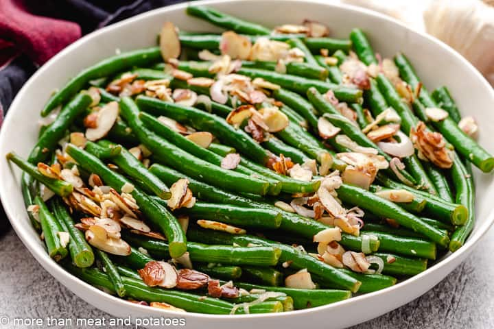 The green beans almondine served in a white bowl.