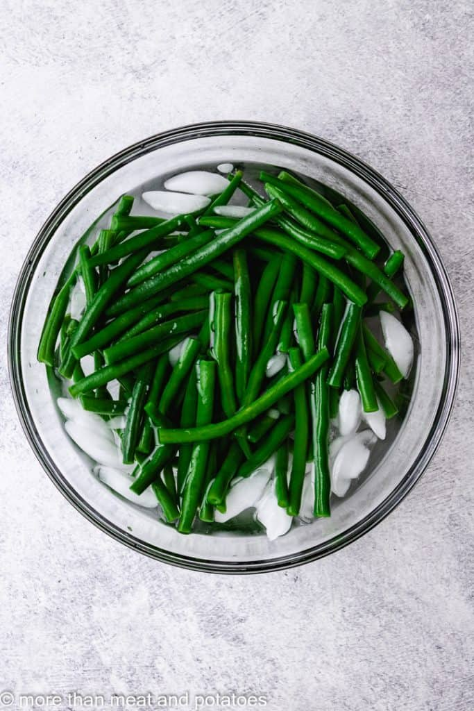 Boiled green beans chilling in an ice bath.