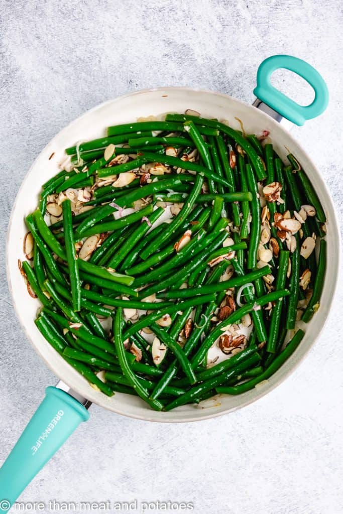 The string beans added to the skillet.