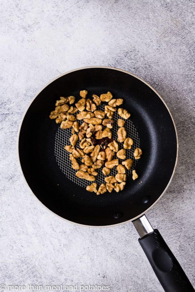 Walnuts toasting in a small saucepan.