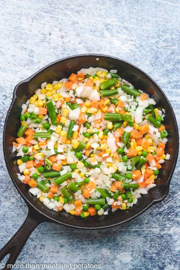 Mixed vegetables cooking in a cast iron skillet.