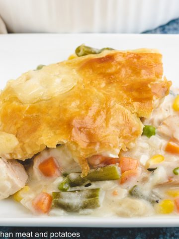 A serving of turkey pot pie with puff pastry on a plate.
