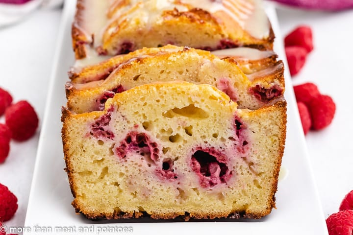 White chocolate bread with raspberries on a white platter.