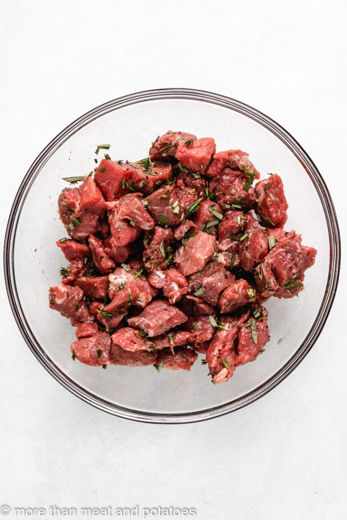 Stew meat and spices tossed together in a bowl.