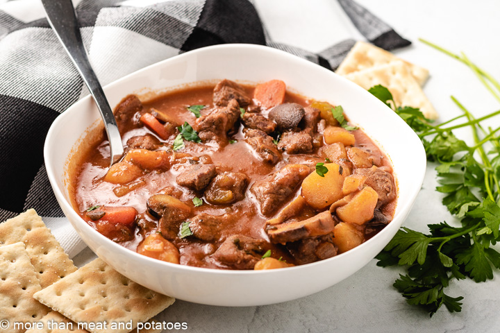 Cooked beef stew with tomato sauce in a white bowl.