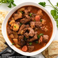 An aerial view of the stove-top beef stew with crackers.