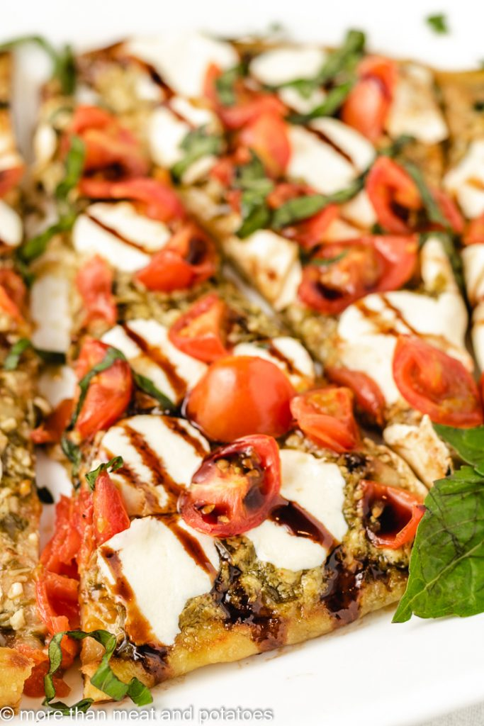 Close up of tomato mozzarella basil flatbread.