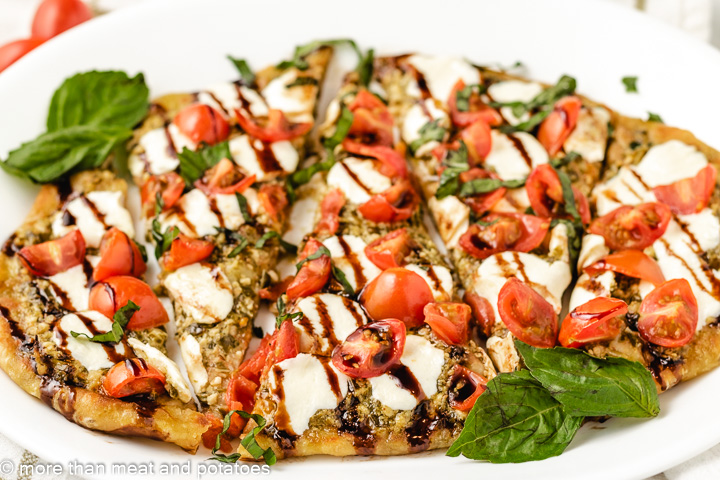 Sliced flatbread with tomatoes and mozzarella.