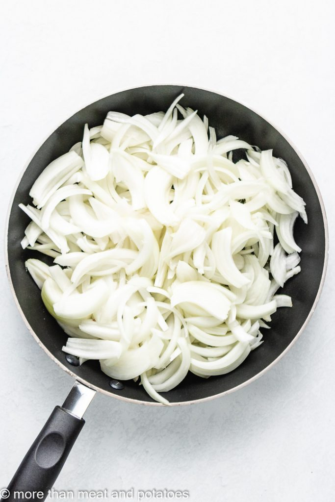 Olive oil and sliced onions in a sauté pan.