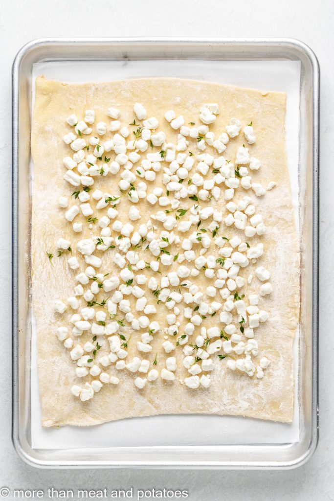 Seasoned goat cheese sprinkled over raw puff pastry dough.