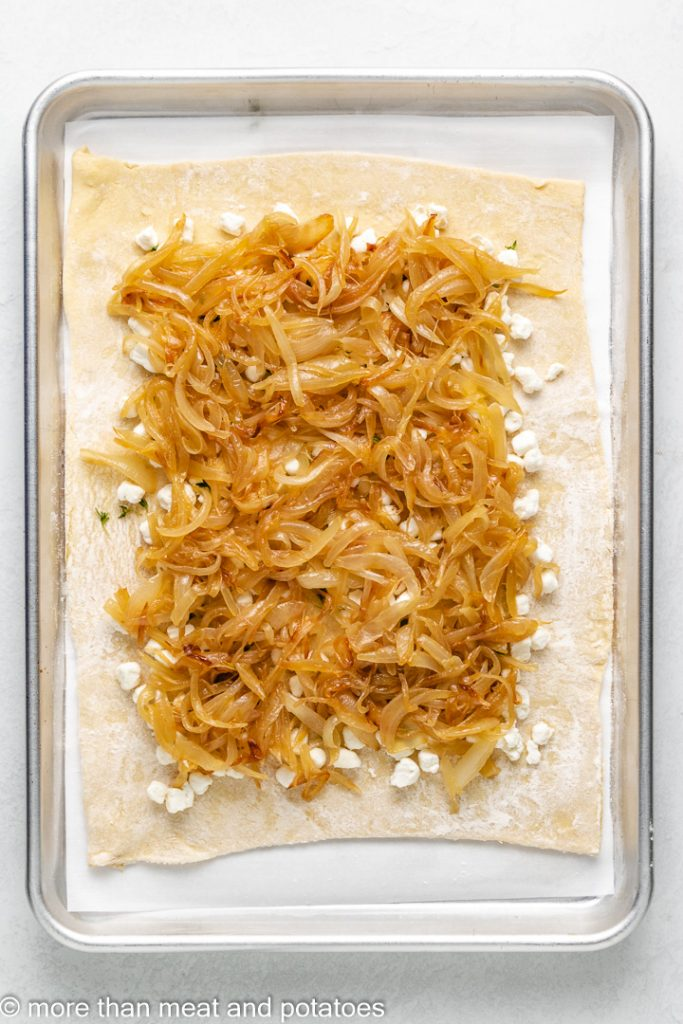 The cooked onions sprinkled over the cheese.