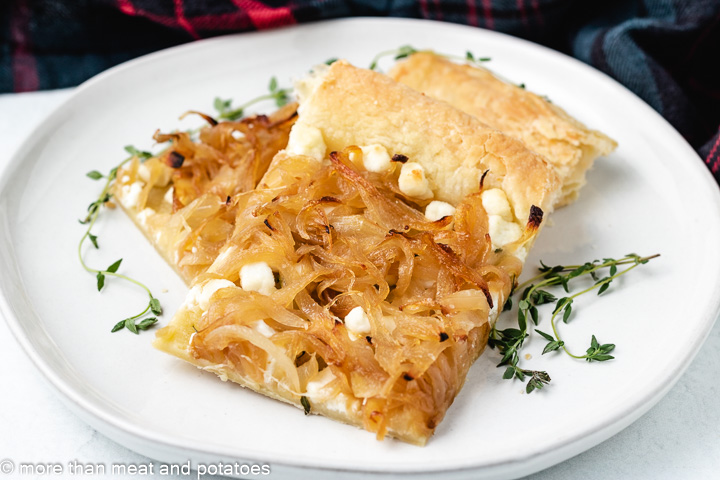Two slices of caramelized onion tart on a plate.