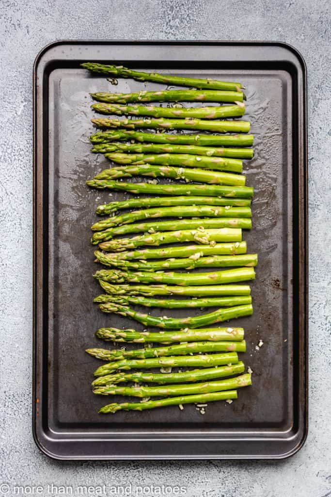 Trimmed asparagus spears on a sheet pan.