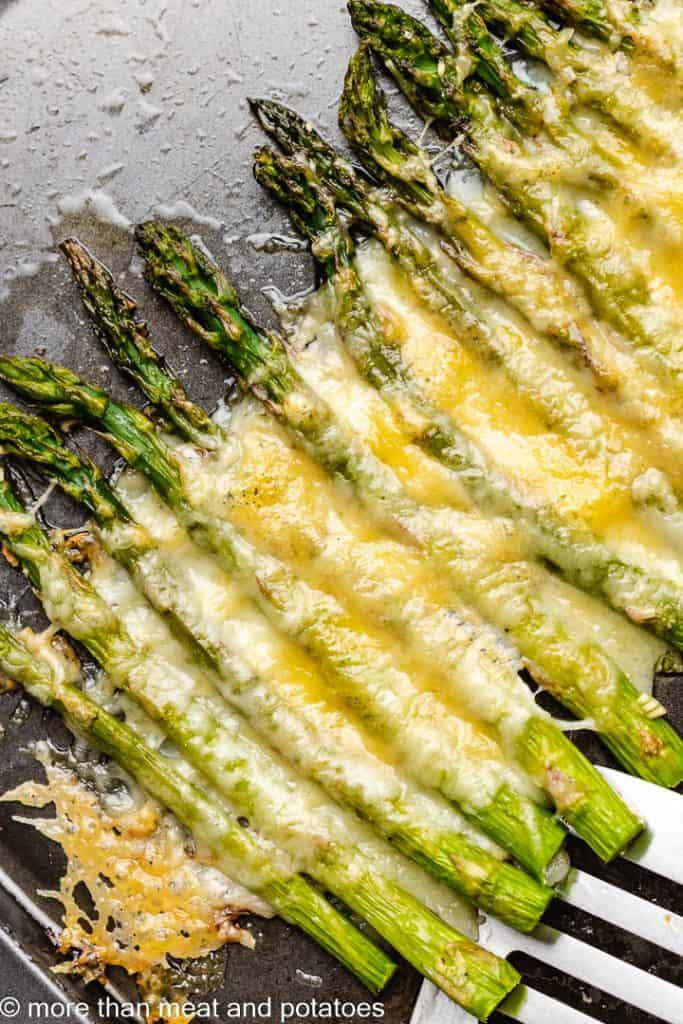 An up-close view of cooked asparagus with melted cheese.