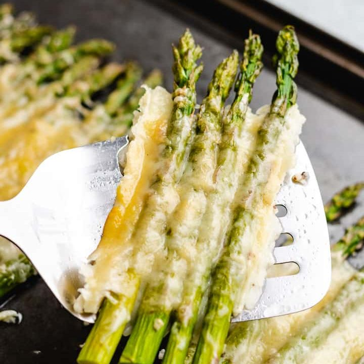 A metal spatula lifting cheesy asparagus from the sheet pan.
