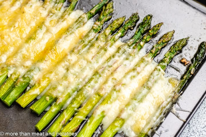 Roasted asparagus on a sheet pan covered with melted cheese.