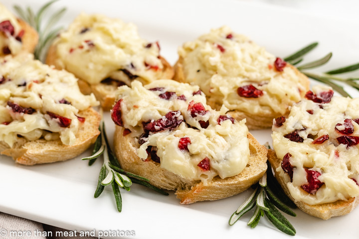 The cranberry brie crostini bites served on a white platter.