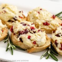 Five cranberry brie crostini appetizers on a plate.