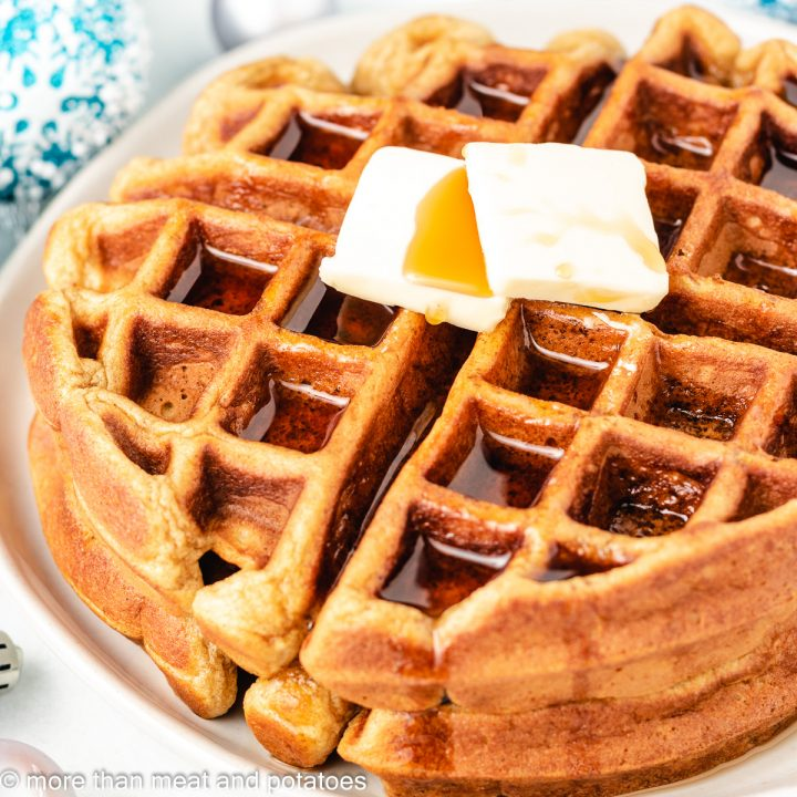 Two stacked eggnog waffles with butter and syrup.