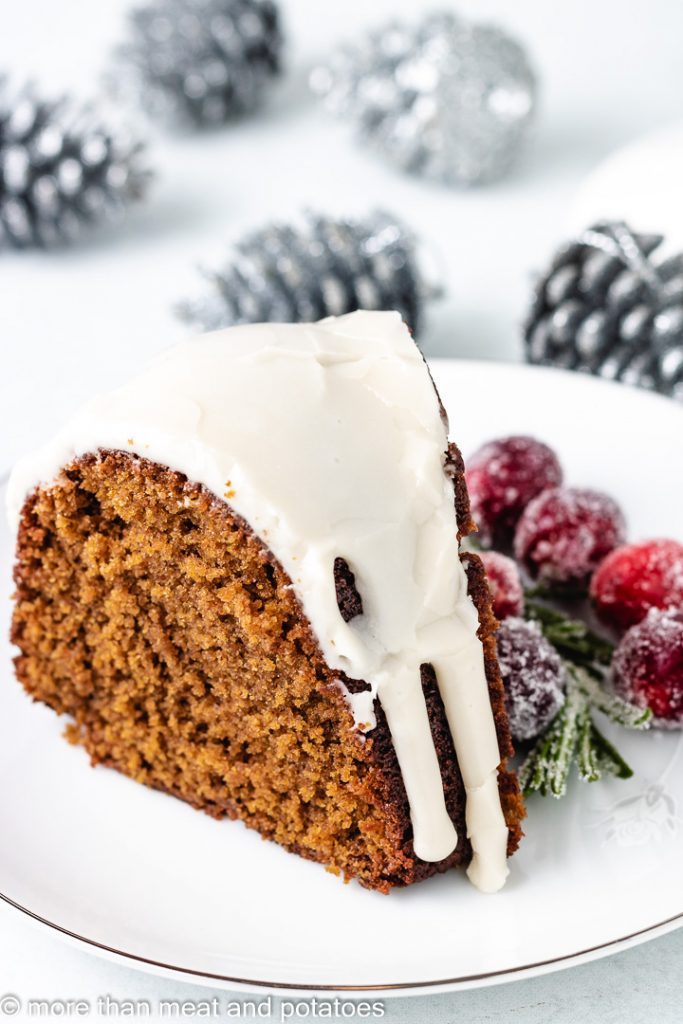 Slice of gingerbread cake next to silver pinecones.