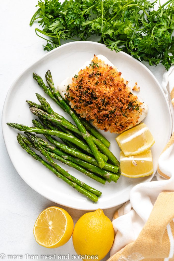 Top down view of baked cod with panko on a plate.