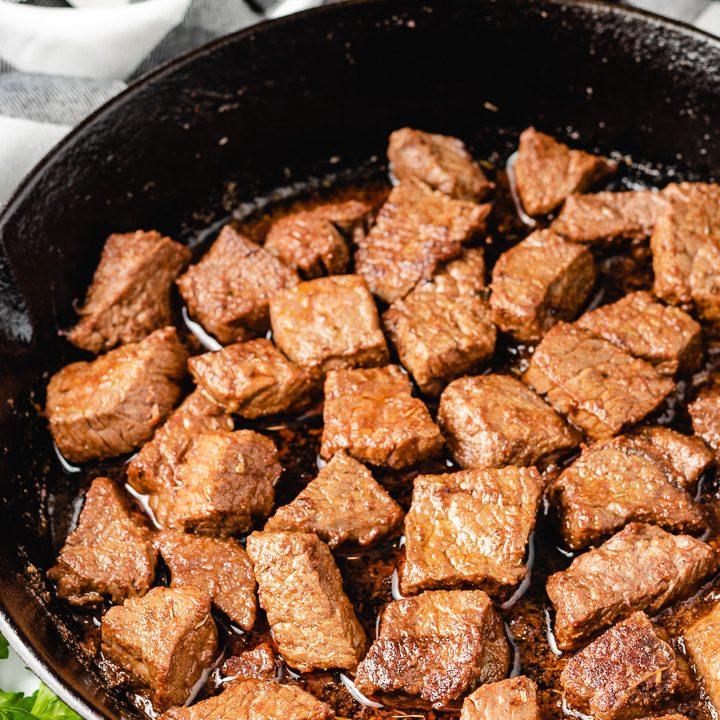 Close up photo of cajun steak bites in a pan.