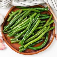 Top down view of Honey Garlic Green Beans on a wooden plate.