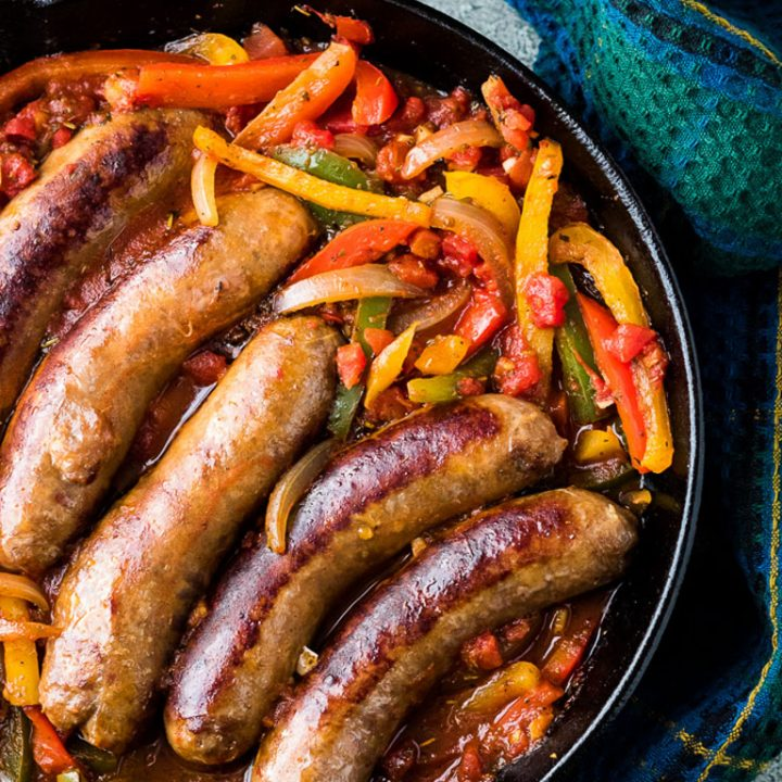 Top down image of Italian sausage and peppers in a cast iron skillet.