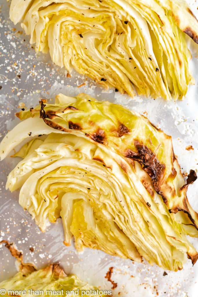 Roasted cabbage wedge on a baking sheet.