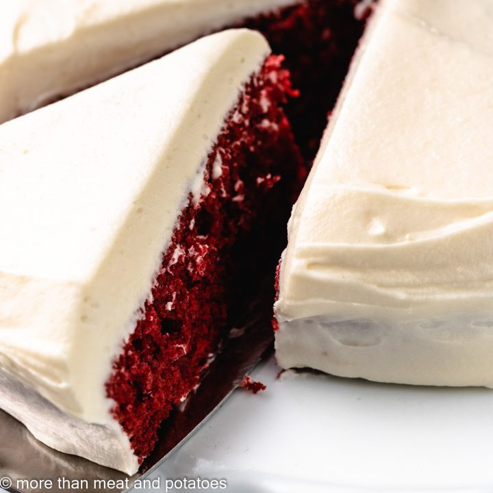 Slice of red velvet cake being pulled from the whole cake.