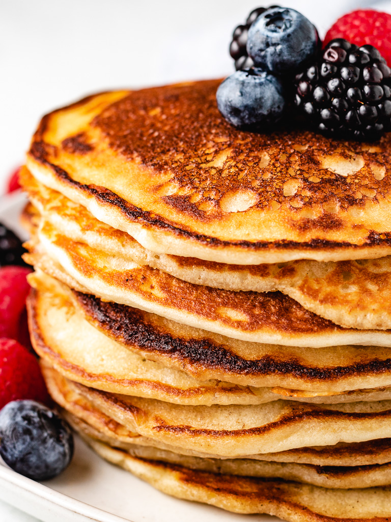 Stack of sourdough starter pancakes with fresh berries.