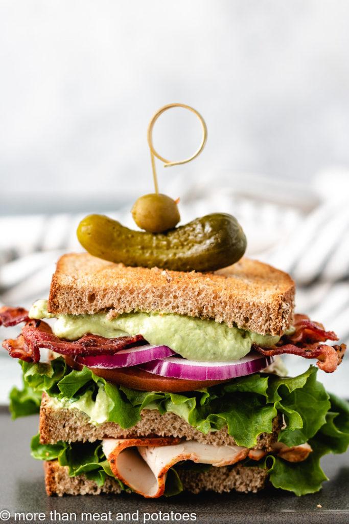 Turkey sandwich with avocado dressing and bacon.