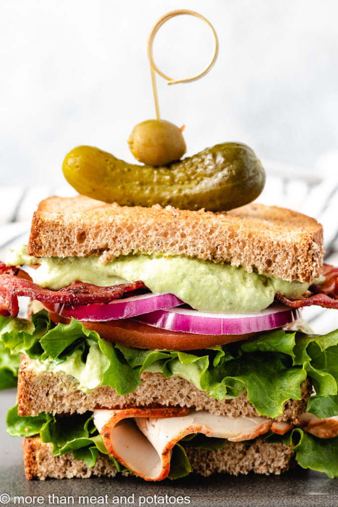 Turkey avocado club topped with a pickle and olive.