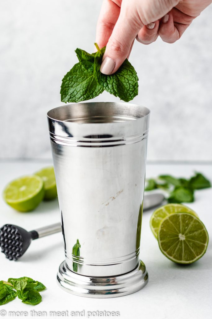 Fresh mint leaves being added to a cocktail shaker.
