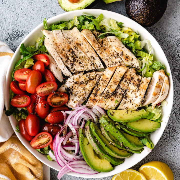 Top down view of chicken, tomatoes, and avocado on a salad.