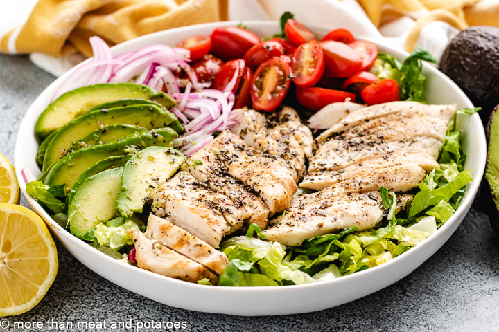 Chicken, avocado, and tomatoes on a salad.