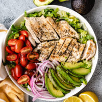 Chicken avocado salad in a gray dish with lemons.