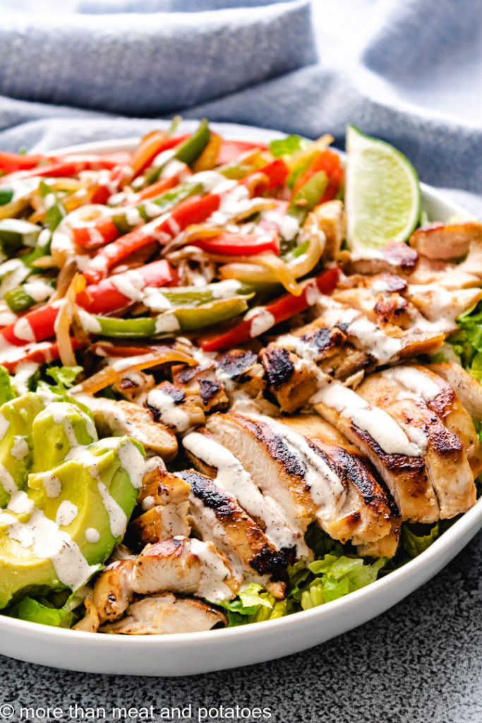 Chicken fajita salad with peppers and onions.