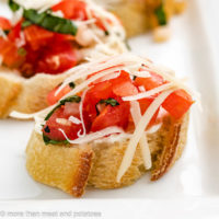 Bruschetta topped with Parmesan cheese and cream cheese.
