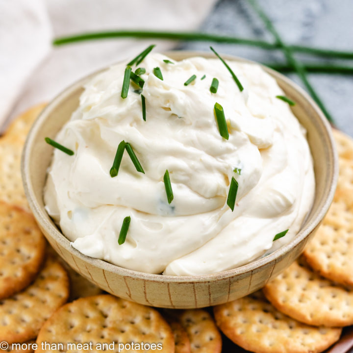 Garlic dip with crackers and fresh chives.