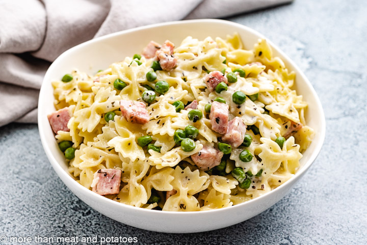 White bowl with pasta and a light cream sauce.