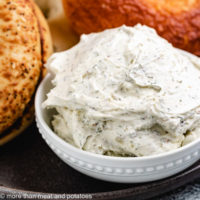 Garlic herb cream cheese in a small, white dish.