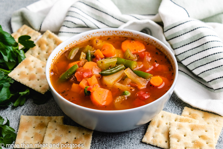 Homemade vegetable soup with frozen vegetables in a blue bowl.