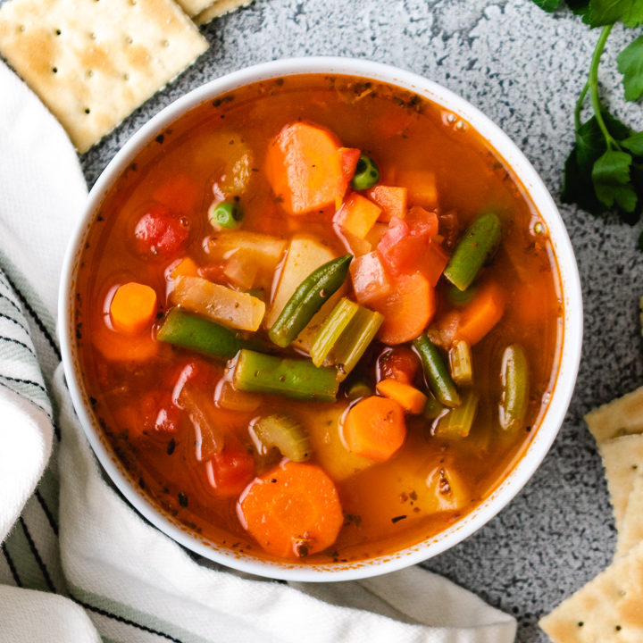 Top down view of vegetable soup with crackers.