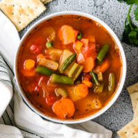 Top down view of vegetable soup in a bowl with crackers.