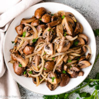 Top down view of mushrooms and onions in a bowl.