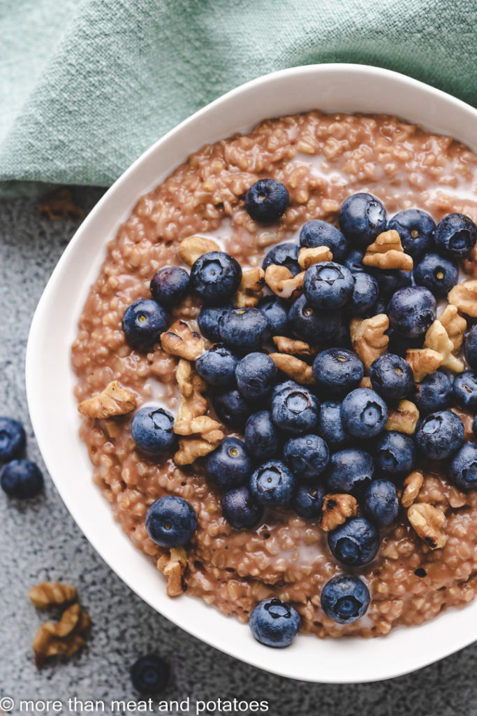 Top down view of steel cut oats topped with blueberries.