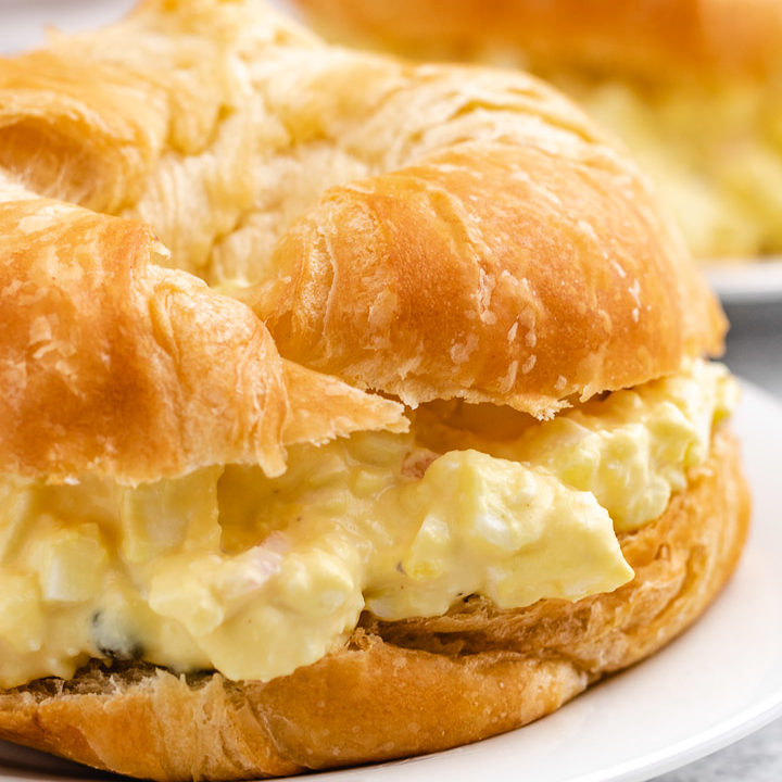 Close up photo of egg salad on a croissant.