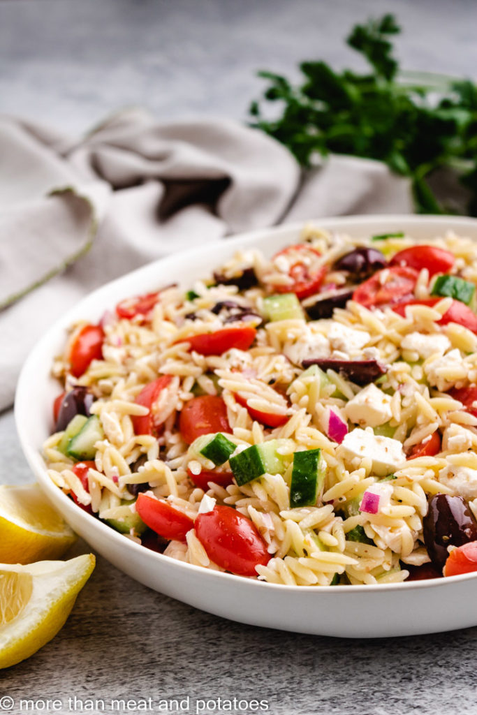 Greek orzo salad in a gray bowl.
